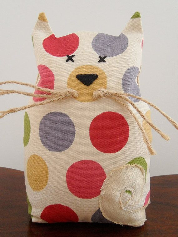 These kittys have a lot of personality and are a cute way of propping open a door or holding up some books. They are made in a lovely spotty cotton fabric, with a sand colour linen blend fabric used for the back and base. They have a black felt hand stiched nose, hand stiched eyes, an appliqué shiney gold tail and whiskars made from natural jute twine. They measure approx : 20cm high x 12cm wide x 8 deep They are sent out partially filled with hollow fibre wadding to ensure the best fin...