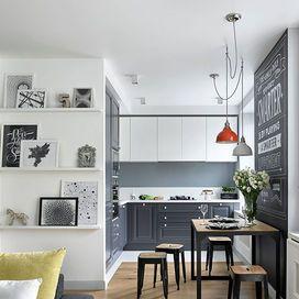 Foto e stampe a tutta parete dietro al divano. In cucina: sotto più scuro e sopa pensili chiari. Colori neutri. Lampadario meno ingombrante