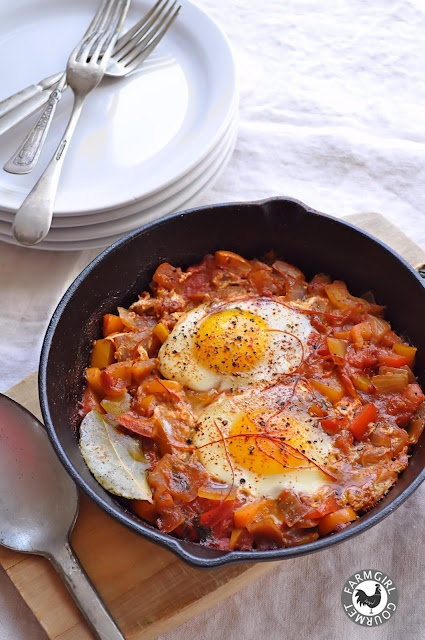 Shakshuka is a dish of eggs poached in a sauce of tomatoes, chili peppers, onions, often spiced with cumin.