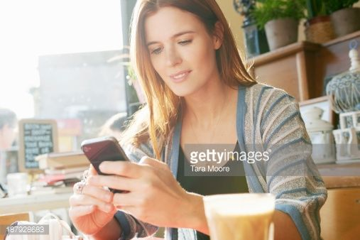 Foto de stock : woman in cafe texting with mobile phone