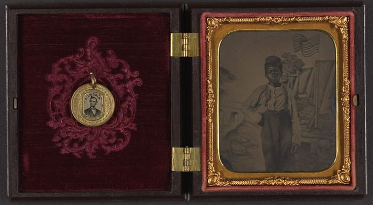 An unidentified African-American boy standing in front of a painted backdrop showing American flag and tents; (left) campaign button with portraits of Lincoln on one side and Johnson on the opposite side are attached to the inside cover of the case.