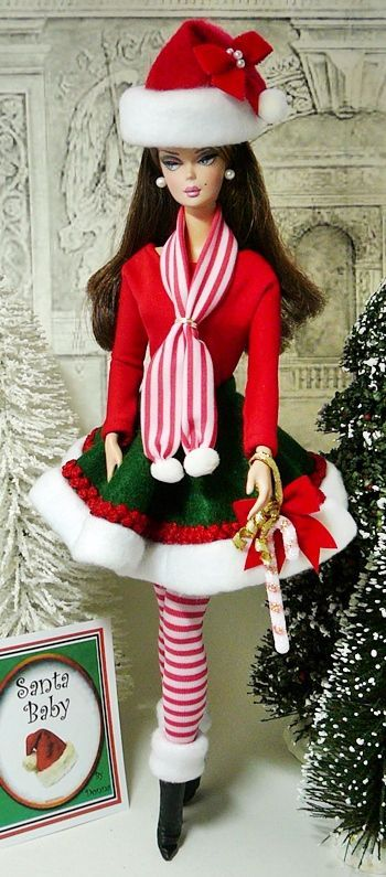 "Donnas-Doll-Designs This festive Holiday ensemble features a green felt skirt trimmed with white fleece and red braid. The skirt is worn over a red knit bodysuit. Accessories include a long red & white striped scarf and matching leggings worn with a pair of black leatherette booties. A rde felt ""Santa"" hat completes the look. Jewelry is a pair of pearl earrings"