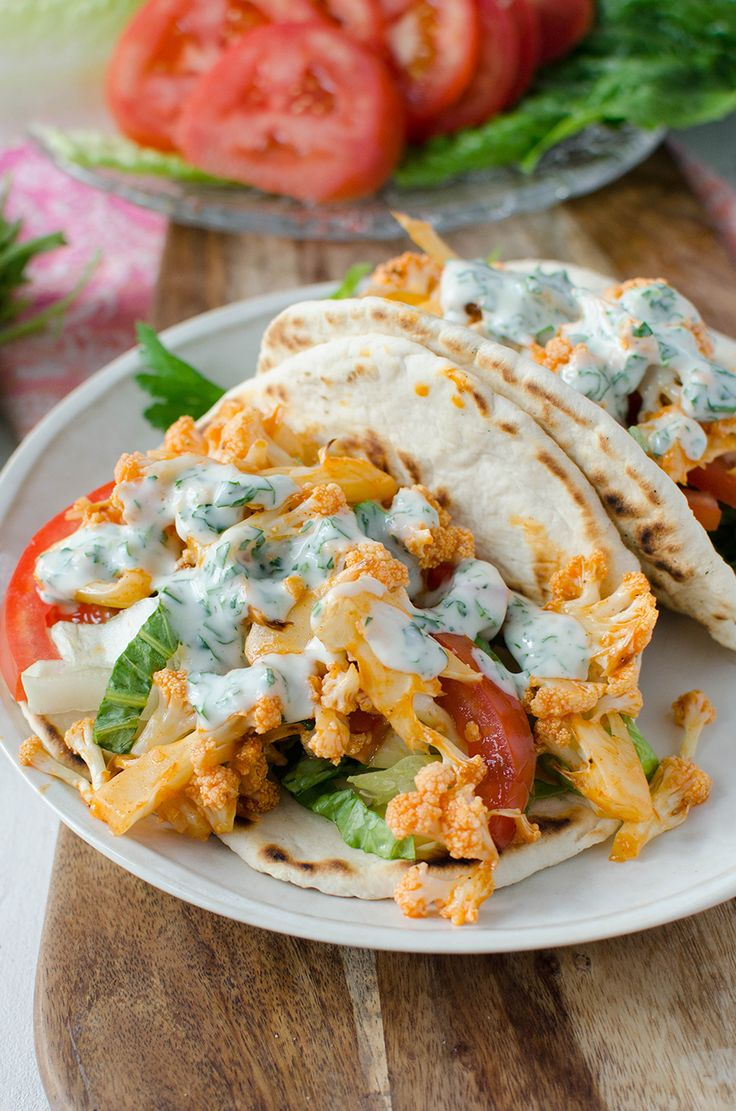 Buffalo Cauliflower Flatbreads! These vegan sandwiches are packed with so much flavor! Roasted buffalo cauliflower on homemade flatbreads. Topped with a simple dairy-free ranch dressing.