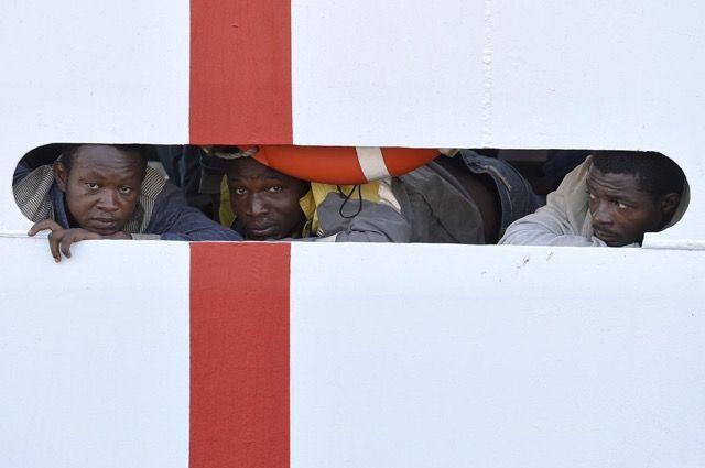 ヨーロッパ移民問題の現状 > イタリア沿岸警備隊の船からの下船を待つ人々。2015年8月29日、イタリア・シチリア。