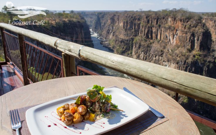 ULTIMATE AFRICA  DINE FEATURE: THE LOOKOUT CAFÉ  Perched 120m above the turbulent rapids of the Zambezi River, overhanging a giant chasm of the Batoka Gorge, just downriver of the iconic Victoria Falls Bridge, which forms part of it's spectacular backdrop.