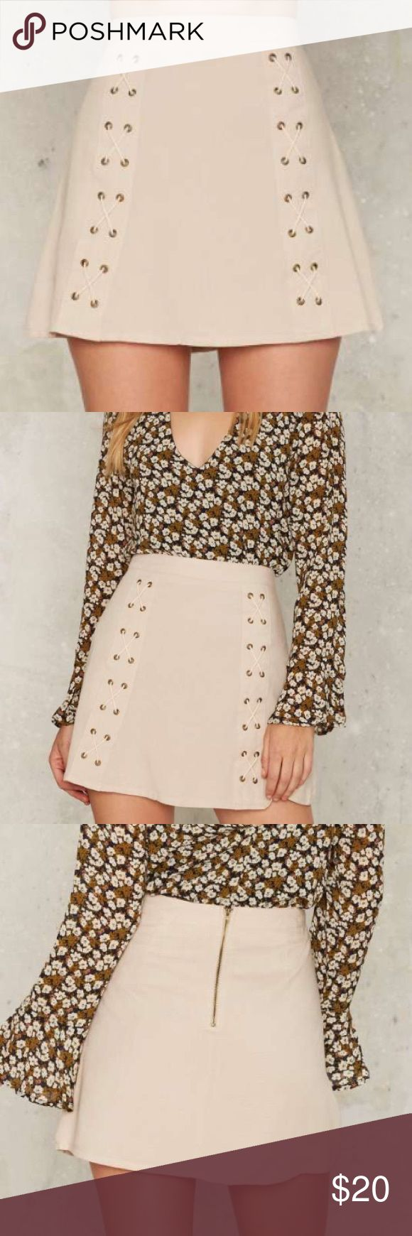 Double Cross Me Lace-Up Skirt The Double Cross Skirt is beige and features a high-waisted fit, mini length, gold zip closure at back, and double lace-up detailing at front. Fully lined. Sadie & Sage Skirts Mini