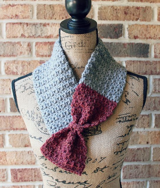 This looks pretty easy to make.. Just a simple scarf with 2 colours, then tie a band around to make the bow..maybe put a button behind the bow into the other side of the scarf??