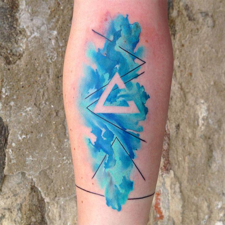 Tatuagem criada por Ondrash da República Tcheca.    Espaço negativo e aquarela no braço.