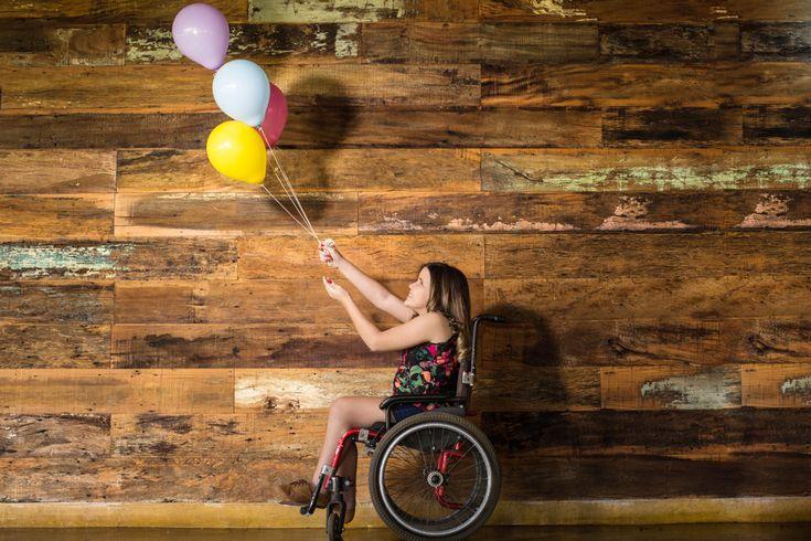 sentada na sua cadeira de rodas e brincando com os baloes