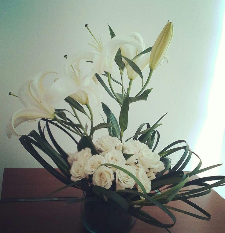 Lirios y rosas en un arreglo floral moderno