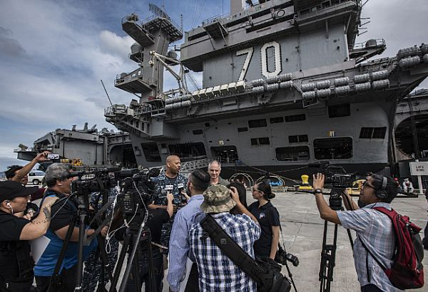 Rear Adm. John Fuller, commander, Carrier Strike Group 1, left, and Capt. Doug Verissimo, commanding officer of the Nimitz-class aircraft carrier USS Carl Vinson (CVN 70), address the media after pulling into Naval Base Guam.