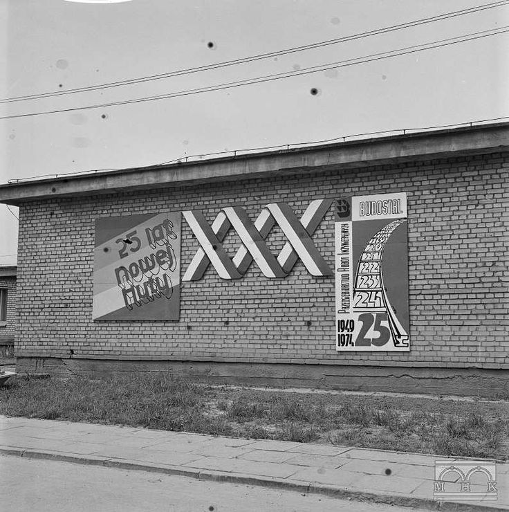 Żelbet - Łęg twentieth anniversary, author: Janusz Podlecki, 1970, Nowa Huta (Cracow). The picture shows storey building, which has been hung posters on the 25th anniversary of Nowa Huta. Two posters flank the inscription XXX made with Polish flags. The poster on the left side, an inscription 25 YEARS OF NEW HUTY; on the second poster duplicated several times the number 25.
