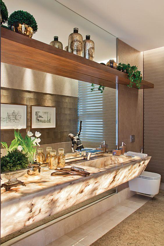 O lavabo, com bancada em ônix iluminado e monocomando Hansgrohe (Vallori).: