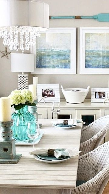 Gray walls but this dining area couldn't be any happier! With blues and whites throughout, this beachy cottage decor is looking glam with colored glass and crystal accented chandelier. Beautiful!