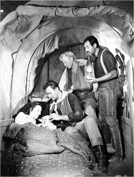 THREE GODFATHERS (1948) - John Wayne, Harry Carey Jr. & Pedro Armendariz come to the aid of Mildred Natwick and her infant child - Directed by John Ford - MGM - Publicity Still.