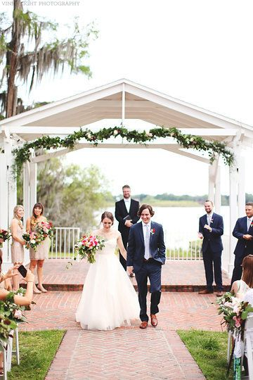 finally mr. & mrs., the happy couple heads down the aisle from underneath a lakeside gazebo dressed with garland of lemon leaf, seeded eucalyptus & plumosa fern peppered with peach stock, pink spray roses, hot pink mini carnations, white football mums, & pink wax flower.
