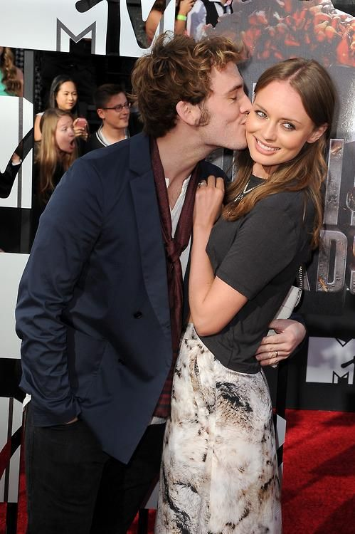 Sam Claflin gives a smooch to his wife Laura Haddock on the red carpet of the MTV Movie Awards.