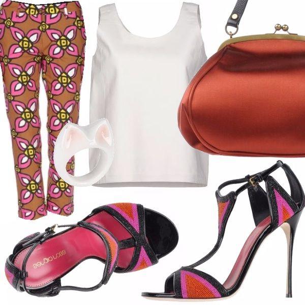 Pantalone capri a fantasia anni 60, top bianco senza maniche, sandali con tacco a spillo e decorazioni con perline allacciati alla caviglia, borsetta in tessuto color arancio, annello sagoma gattino
