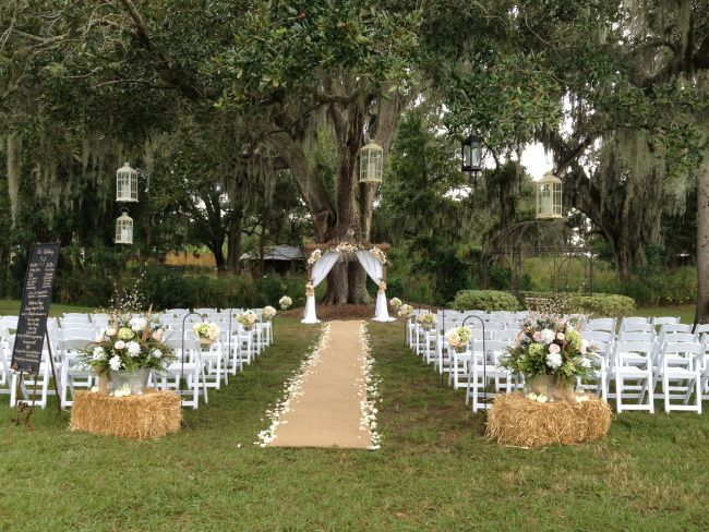 Rustic Wedding Ceremony with haybales, burlap aisle runner, and lanterns in the tree