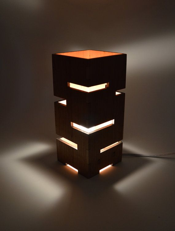 This handmade geometric lamp features multiple linear cut-aways from solid wood for an exciting light display when this piece is illuminated. The