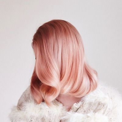 Pastel peachy-pink hair with a brown shadow root