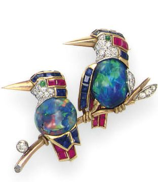 A MULTI-GEM 'LOVEBIRD' BROOCH, BY CARTIER Designed as two lovebirds each with a cabochon opal body, an old European diamond, calibré-cut sapphire and ruby head with a cabochon emerald eye, a polished gold beak, and calibré-cut ruby and sapphire feathers, perched on a gold branch accented by bezel-set diamonds, mounted in gold and platinum Signed Cartier, London