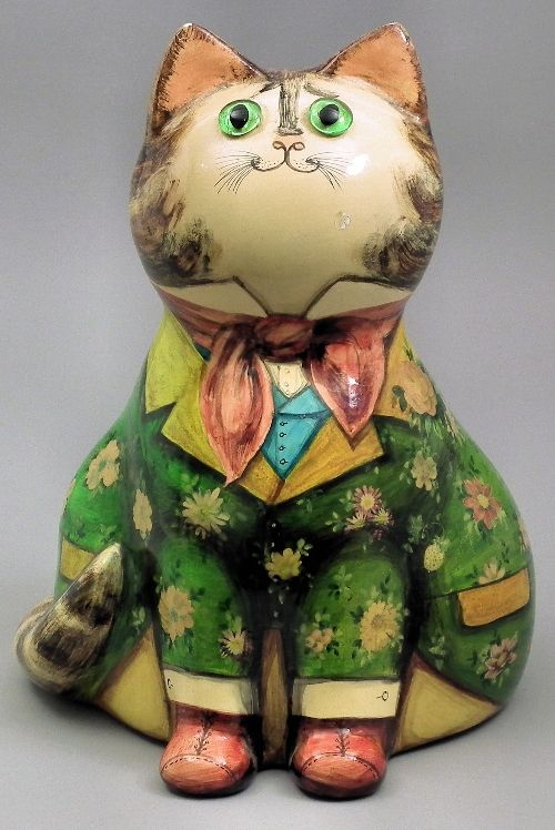 """Joan and David De Bethel - Papier-mache cat with green glass eyes, decorated with pink shawl and with nine line verse to reverse, 7ins high (black painted marks to base - shape no. 1944 and dated 1968) contained in Herbert Johnson """"Cat Box"""""""