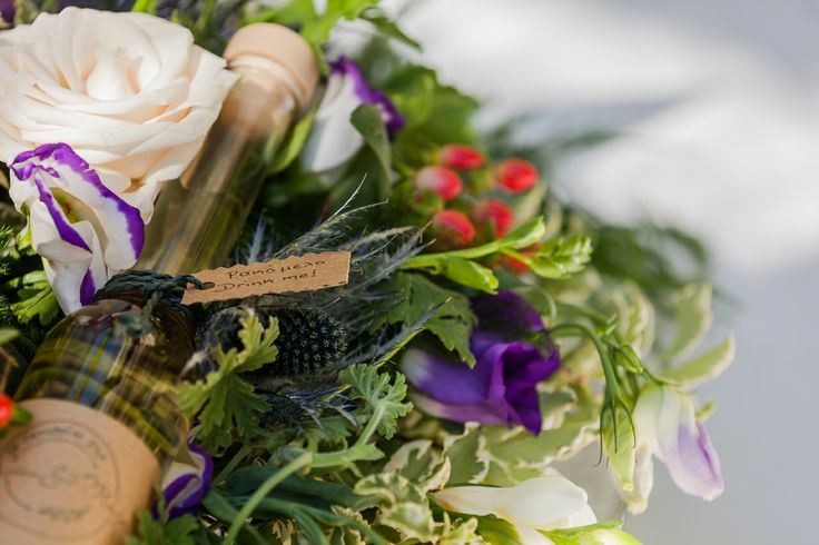 A centerpiece with a custom made bottle of Rakomelo (Greek traditional drink) for a country chic wedding!
