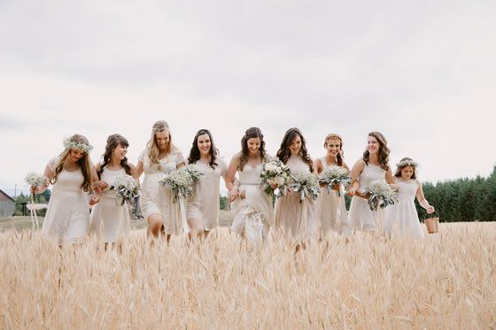 Cheerful bridesmaids walk arm in arm across open fields. Wedding Photographer: Julia Green Photography.