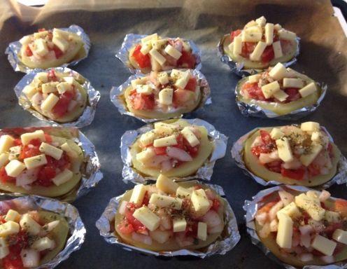 Für die Gefüllten Kartoffelhälften mit Tomaten und Käse die Kartoffeln zu Beginn als Pellkartoffeln kochen, die Haut abziehen und komplett