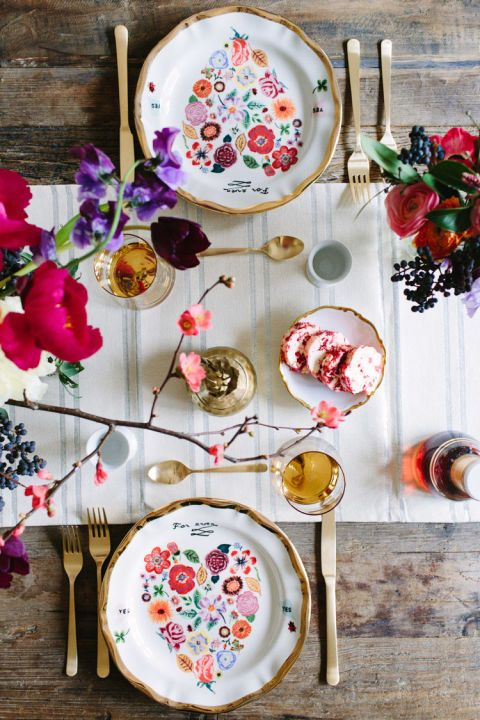 Create a folk-inspired Valentine's Day tablescape with multi-colored floral plates, a striped runner, and gold flatware. Pick up on the colors in your plates with a few colorful bouquets as well.