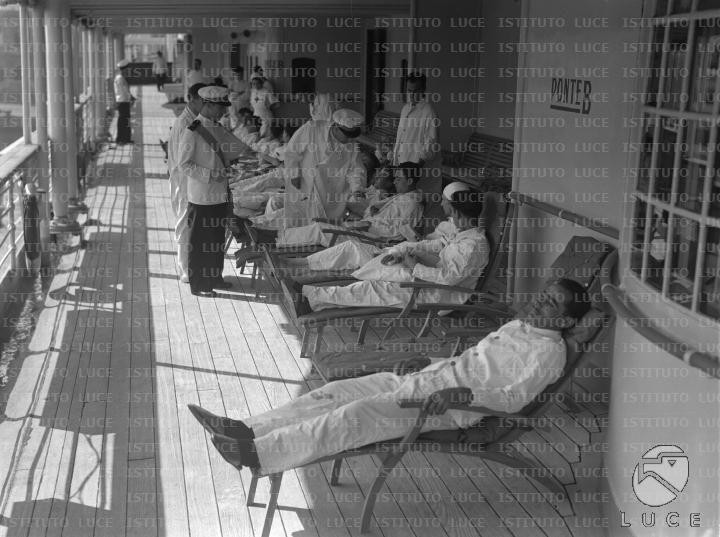 Alcuni feriti riposano su delle sdraio in un ponte laterale della Nave Ospedale California e vengono assistiti dall'equipaggio della nave  RG/RG099/RG00003672.JPG