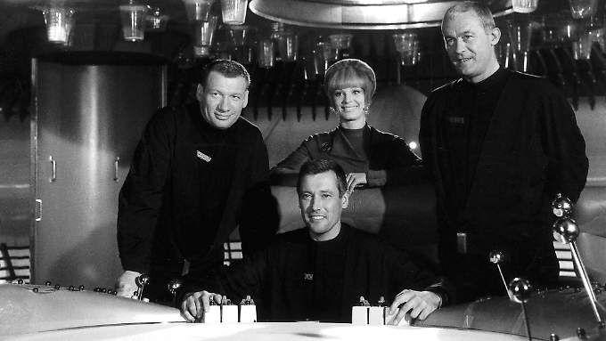 Die Szene aus dem Science-Fiction-Klassiker zeigt (v.l.) Leutnant Mario de Monti (Wolfgang Völz), Major Cliff Allister McLane (Dietmar Schoenherr), Leutnant Tamara Jagellovsk (Eva Pflug) und Leutnant Hasso Sigbjoernson (Claus Holm).
