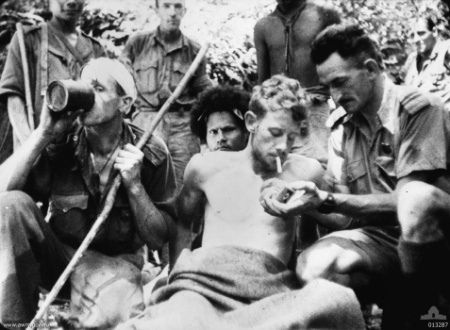 A wounded Australian soldier has his cigarette lit by Salvation Army Chaplain Albert Moore. A Papuan stretcher bearer (known as a Fuzzy Wuzzy Angel) is behind the stretcher.