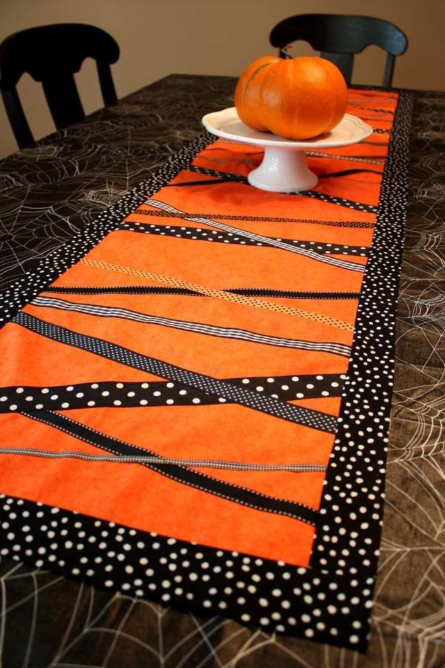 chemin de table en orange et noir à pois blancs et une citrouille orange