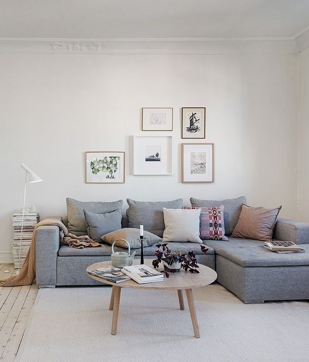 Bright and cheery living room. Light grey sofa, lots of pillows, gallery wall, wooden floors ...