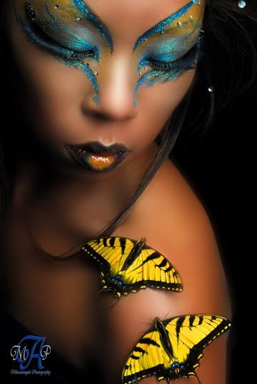 Clear gems accent an artistic butterfly themed blue and yellow make-up look.