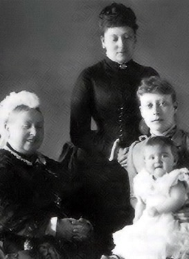 A smiling Queen Victoria, with her daughter Princess Beatrice (standing), her grand-daughter Princess Victoria of Battenberg (nee, of Hesse and by Rhine) and her great-granddaughter Princess Alice of Battenberg.  Little Alice went on to marry Andrew of Greece and Denmark and became the mother of Prince Phillip, Duke of Edinburgh and consort of Queen Elizabeth II.