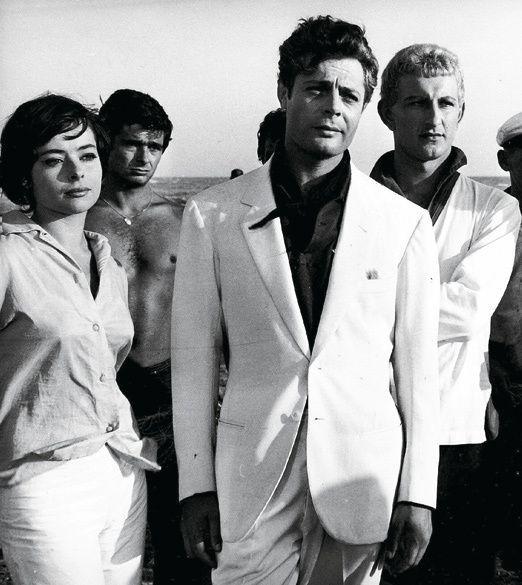 Marcello Mastroianni in a white suit. La Dolce Vita final scene by Federico Fellini (1960)