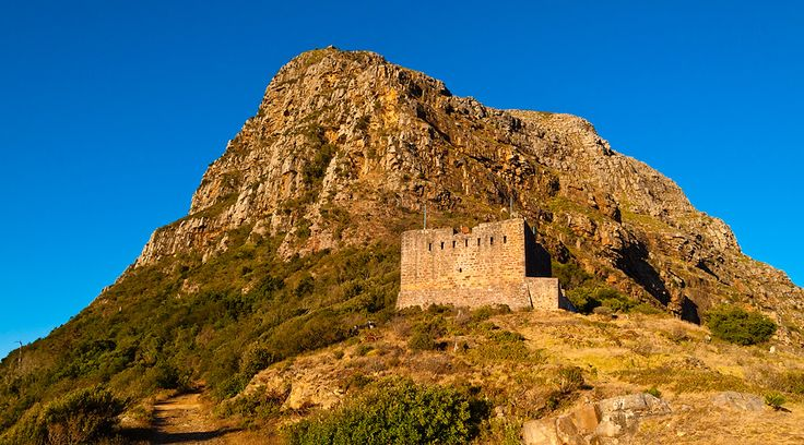 The King's Blockhouse against Devil Peak - Table Mountain - Cape Town. The Devil's Peak Mowbray Ridge trail runs along the mountain via its northeastern and very sheer flank rather than using the usual city donkey route to the southern saddle. #Table Mountain #hiking #DevilsPeak #kingsblockhouse