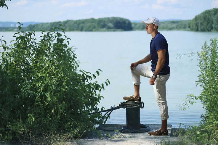 Man wears yacht style outfit. In outfit is Navy Explore T-Shirt by Pharos Apparel, white chinos, white cap, boat shoes and some custom styled bracelets.