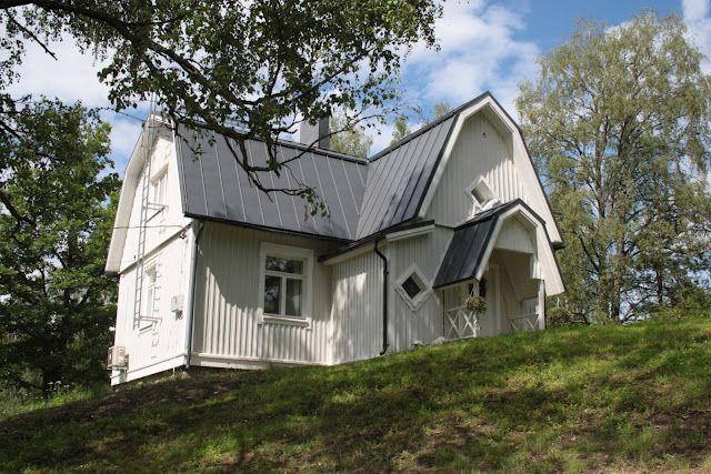 Valkoinen talo tummanharmaa katto.