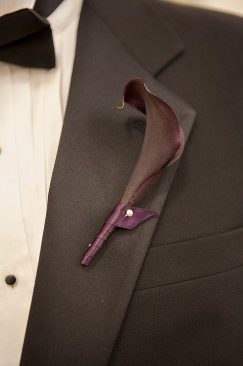 A dark purple Calla lily wrapped in similar color ribbon, is a modern boutonniere option.