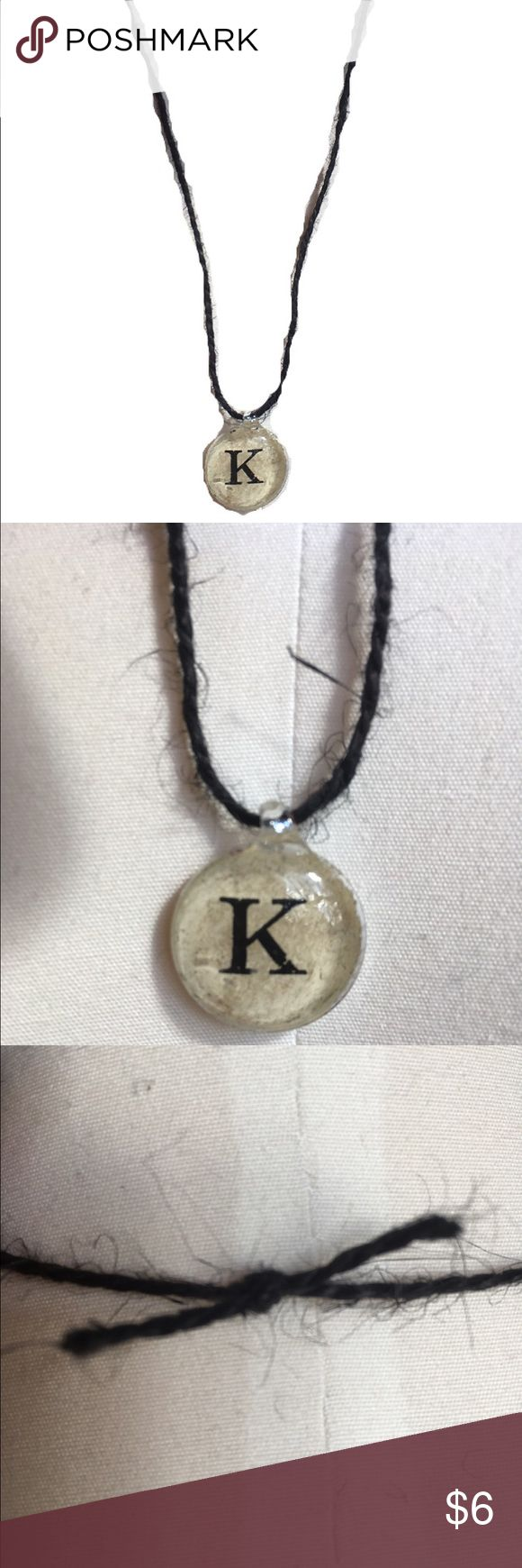 Handmade Black Twine Initial 'K' Necklace Beautiful handmade black twine necklace featuring a silver-coated beige pendant with the initial 'K' in the center. Approx. 13 inches long, including pendant. Only one available. Handmade Jewelry Necklaces