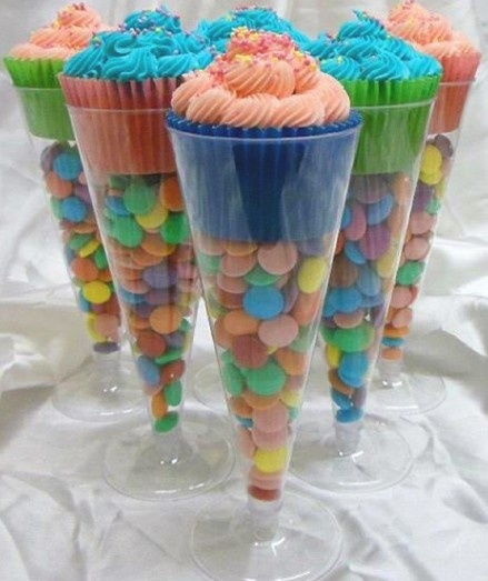 A cupcake sitting on the top of a lolly filled plastic champagne glass – Looks great on the table and is a great alternative to a lolly bag. Thanks Cudo for a great idea