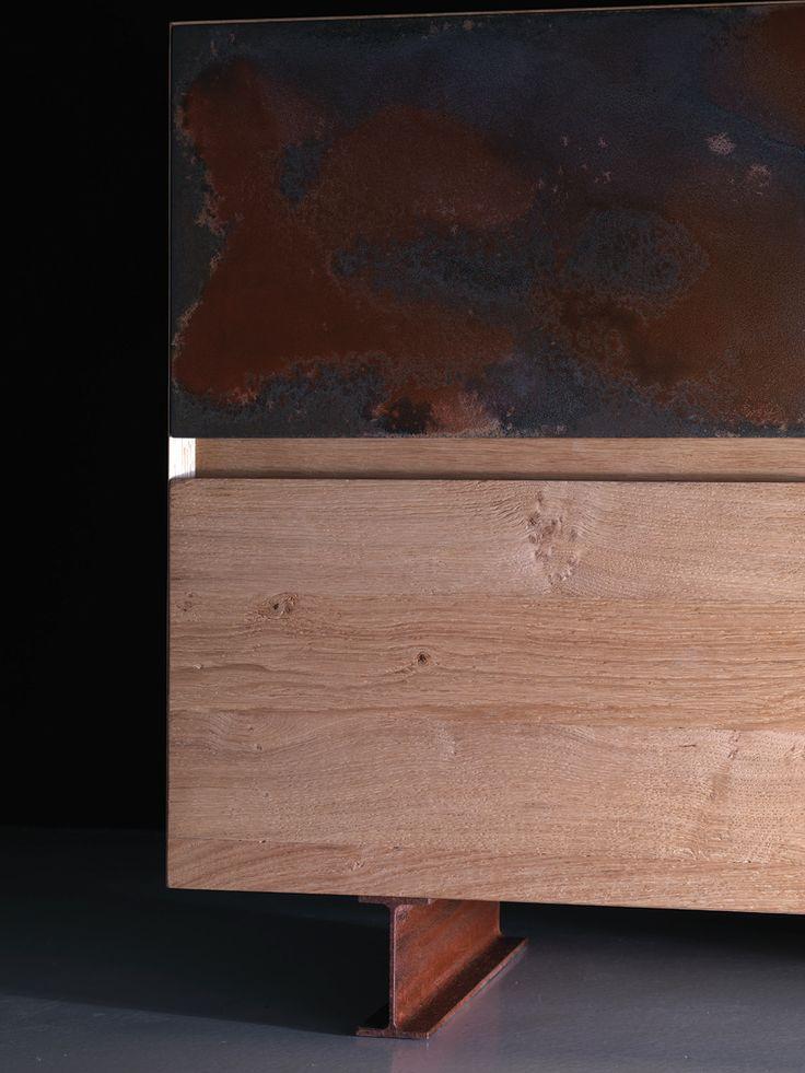 Legno rovere nodato e non spazzolato, finitura color naturale. Struttura del mobile e cassetti s'incontrano sino a formare un angolo di 45°. Numero quattro cassettoni di cui uno con anta finitura in acciaio corten con ossidazione naturale. Piedini realizzati con profilo in metallo a forma I in acciaio corten con ossidazione naturale.