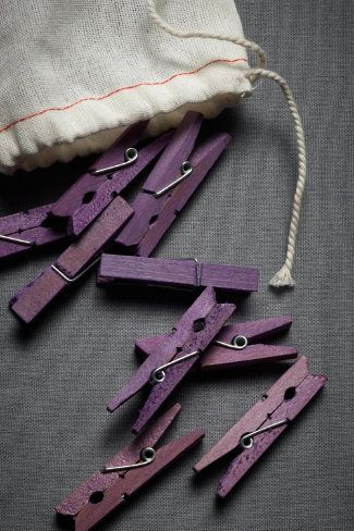 Use Rit Dye to dye clothespins before hanging photos on string. Seal pins with matte polyurethane spray after dying.