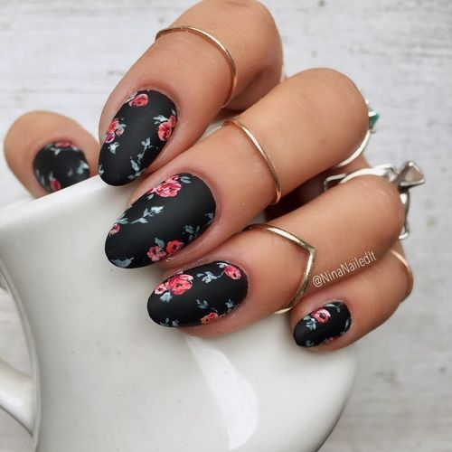 Black manicure with floral pattern.