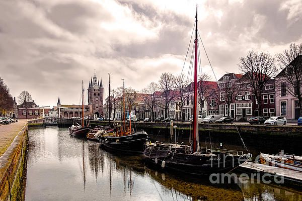This image shows the Zuidhavenpoort of Zierikzee, a small village in Zeeland. Zeeland consists of a group of islands of the Netherlands, Europe. You can see some old ships floating in the foreground and the famous harbor gate in the background. In the village you can find the old maritime architecture which is characterisic for this area of the Netherlands.