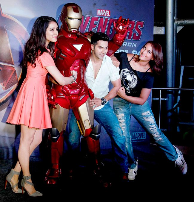Varun Dhawan and Shraddha Kapoor with Sonakshi Sinha pose next to a man wearing an Iron Man costume at the screening of 'Avengers: Age of Ultron'
